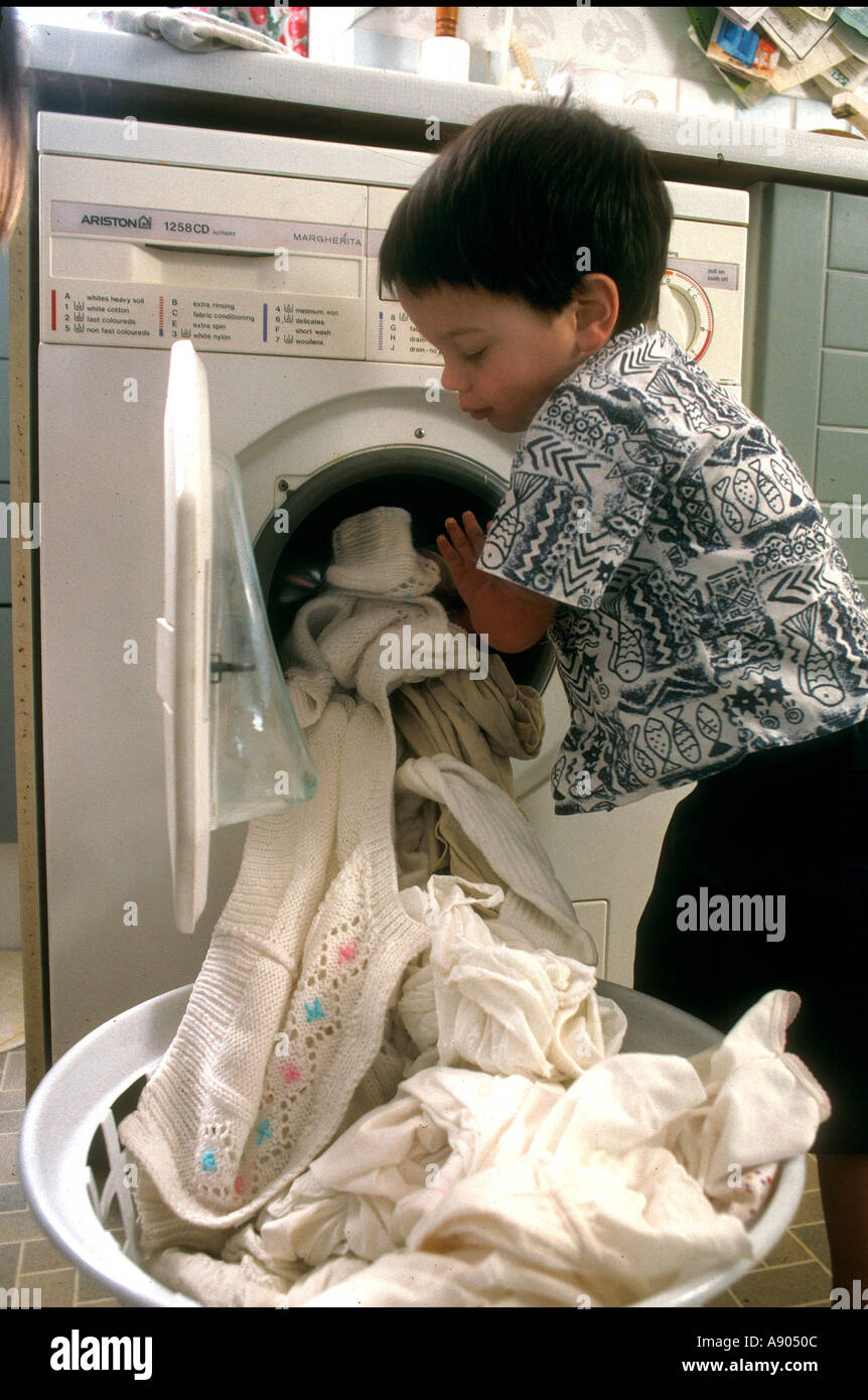 Young Boy Taking Duvet Cover Out Of Washing Machine Stock Photo