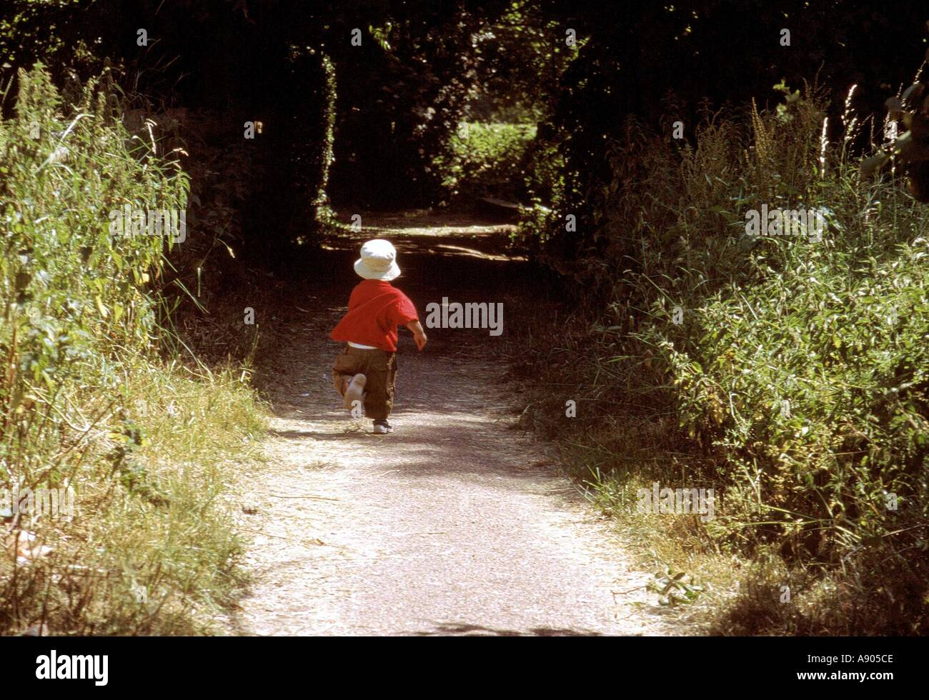 Young boy running down a country path - Stock Image