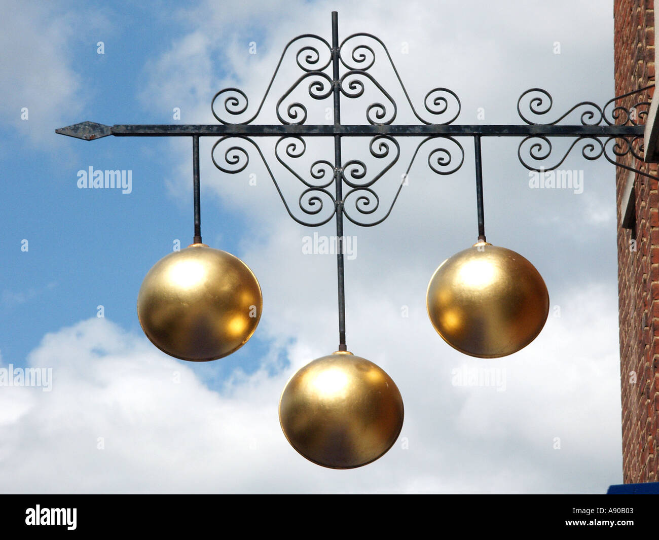 Pawn shop close up of traditional sign of three gold balls above Pawnbroker shop premises supported on ornamental iron bracket England UK - Stock Image