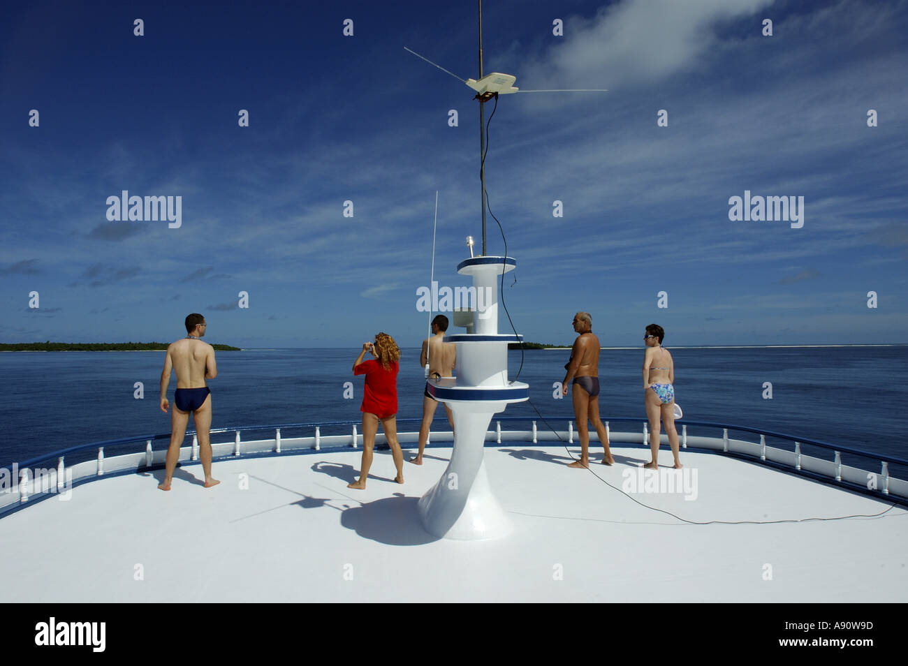 People looking out to sea from the upper deck of a diver's cruise boat, Maldives. Stock Photo