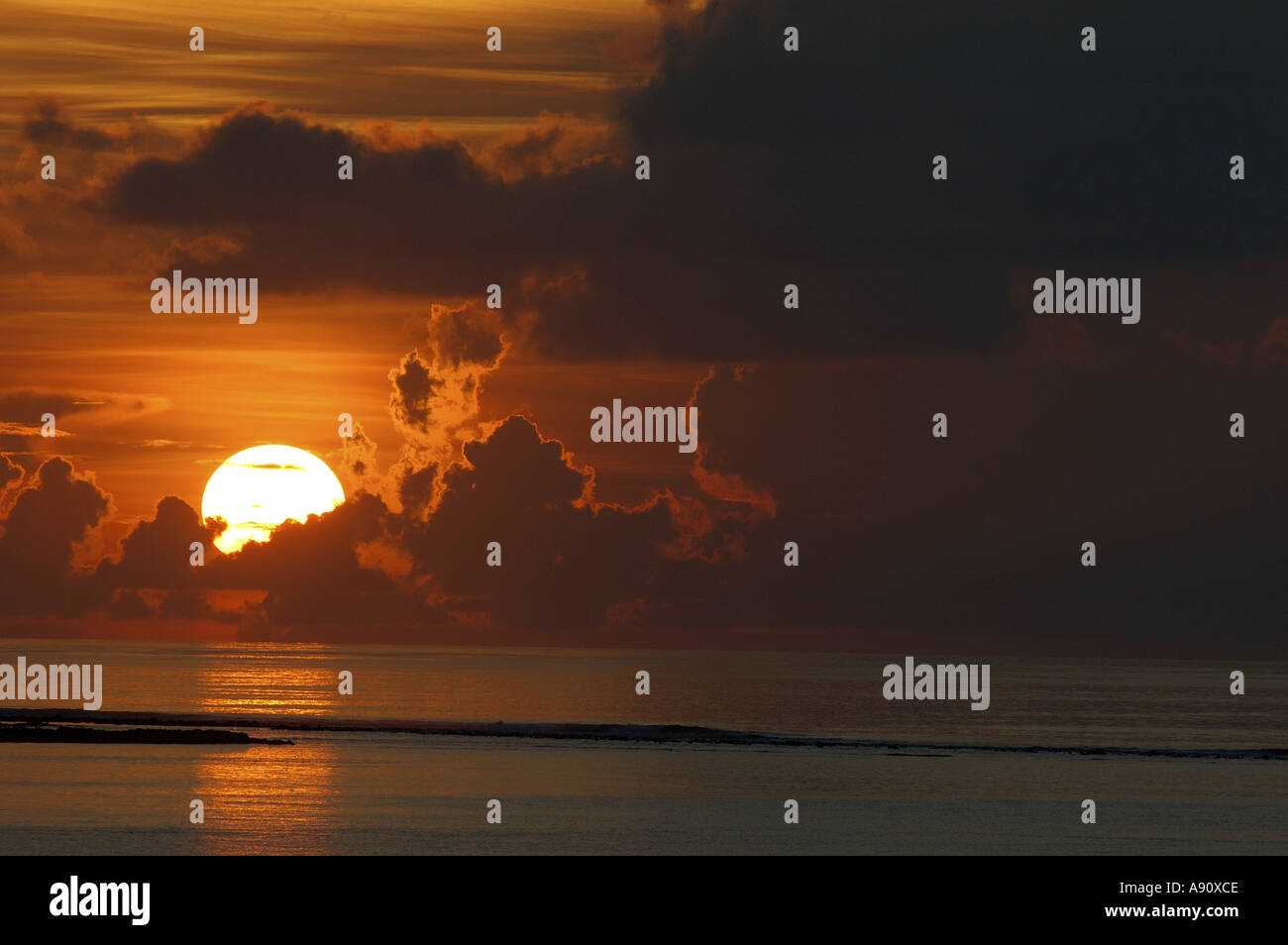 Sunrise - sun rising up over water, clouds and sea with red sky - Stock Image