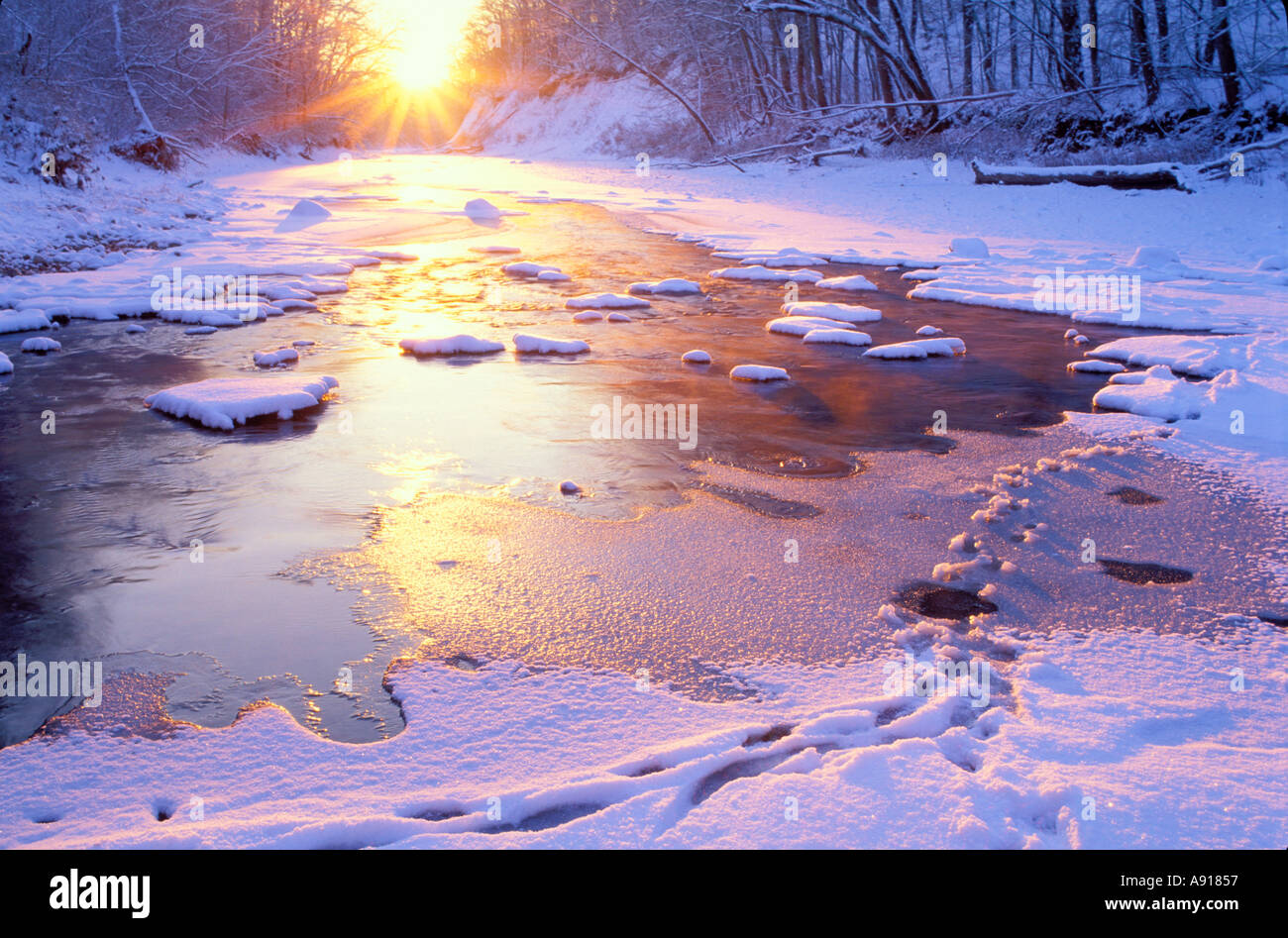 Winter sunrise over the snow covered Middle Fork of the Vermilion River a National Scenic River Kickapoo State Park Illinois - Stock Image