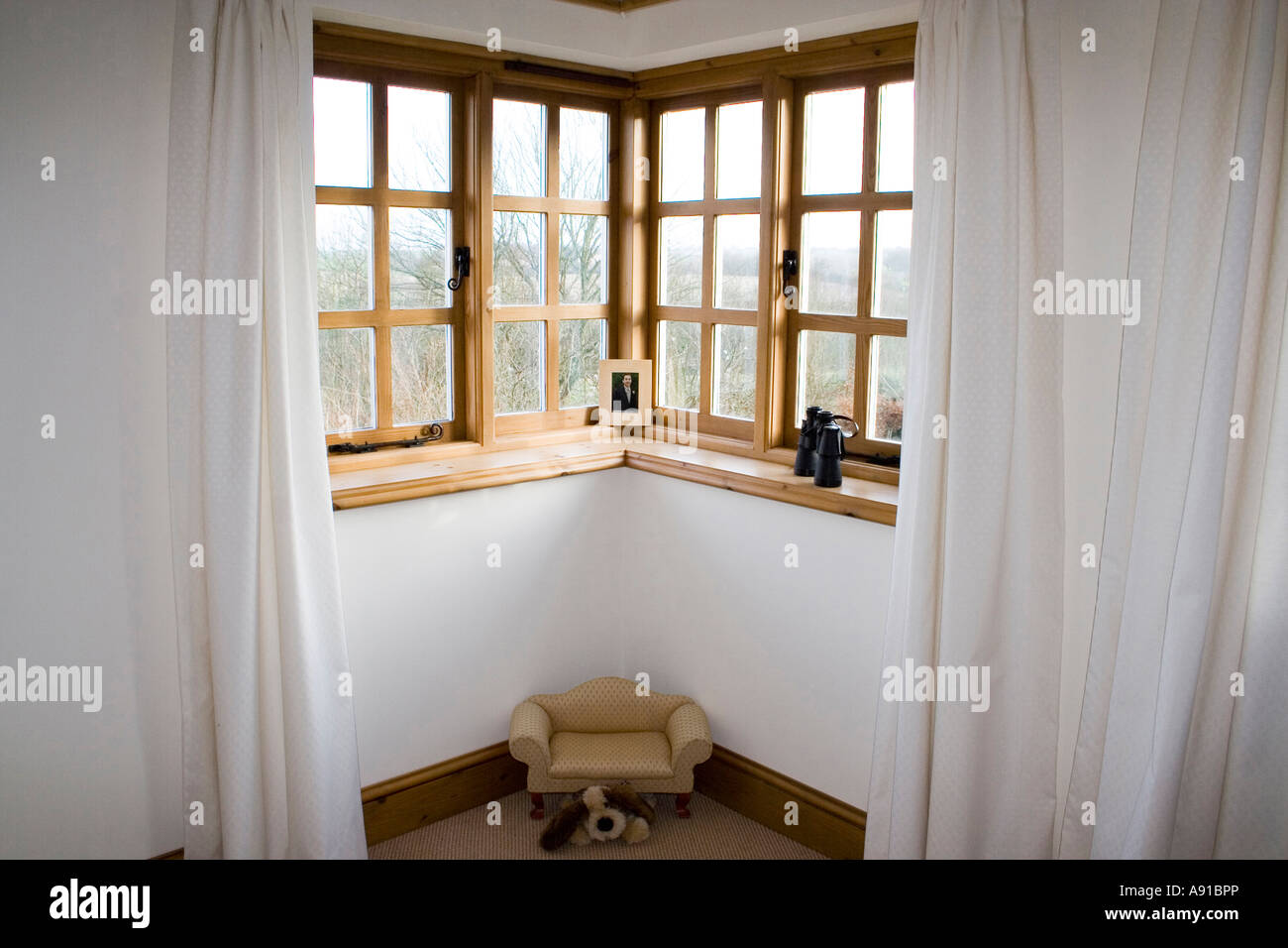 A Corner Window With Wooden Frames And Long White Drapes Or Curtains Stock Photo Alamy