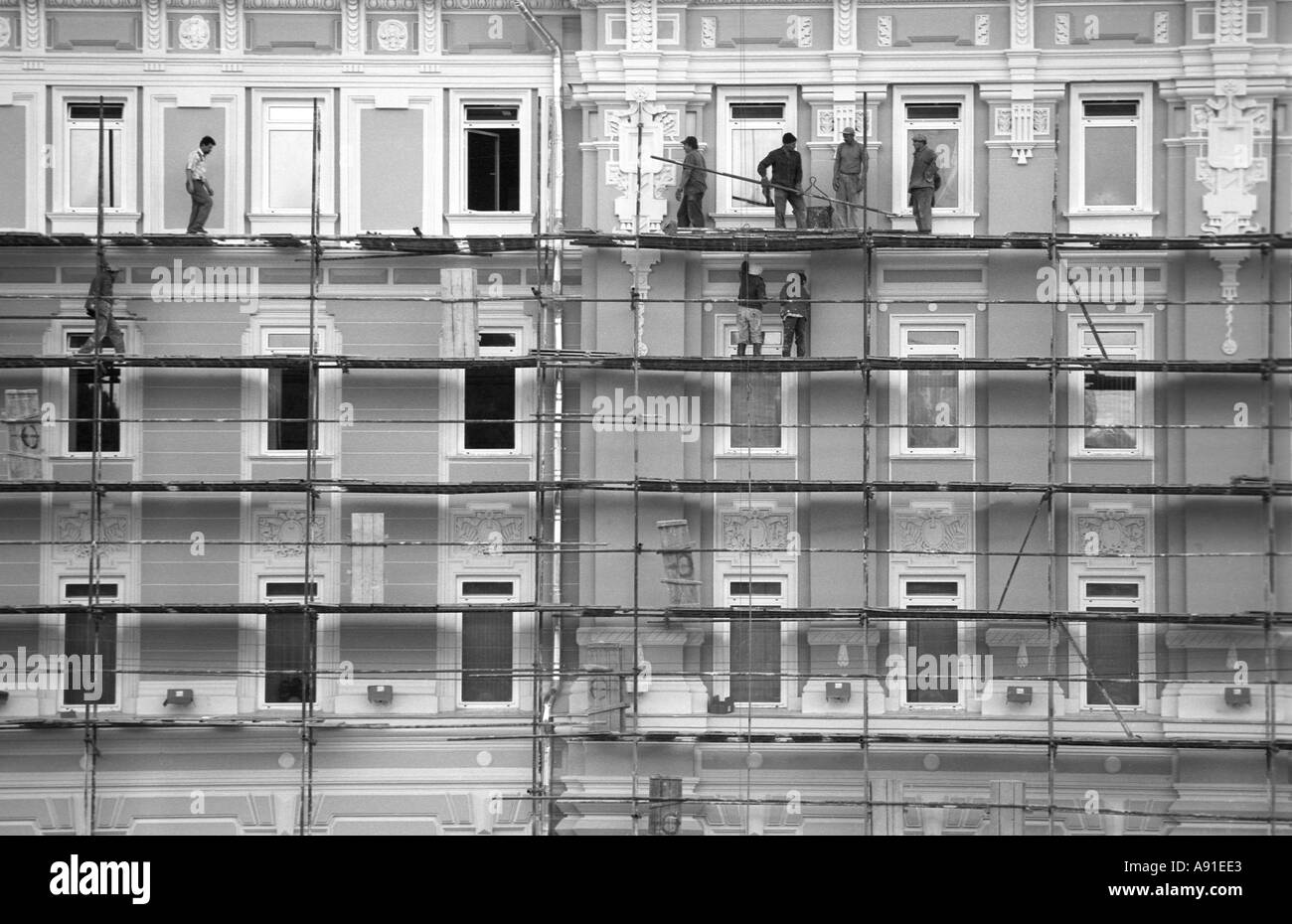 Workers on scaffolding repair an old building in Moscow Russia - Stock Image
