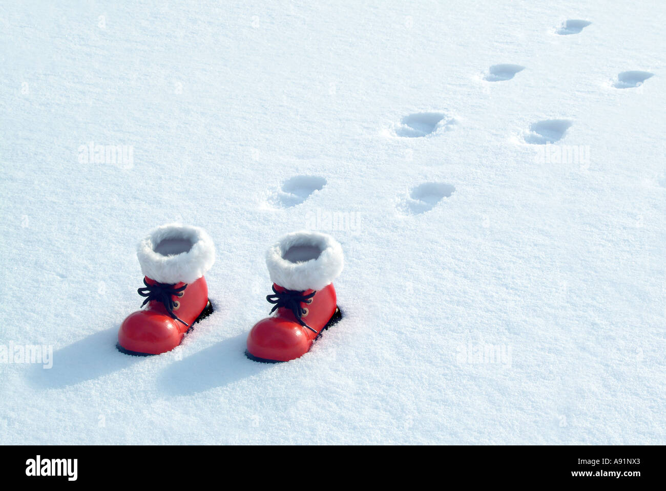 red Santa Claus Shoes in the snow Rote Nikolausstiefel im Schnee - Stock Image