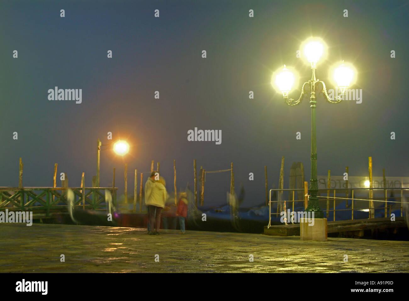 persons at gondola service at night Personen bei den angebundenen Gondeln im Hafen am Markusplatz bei Nacht in Venedig - Stock Image