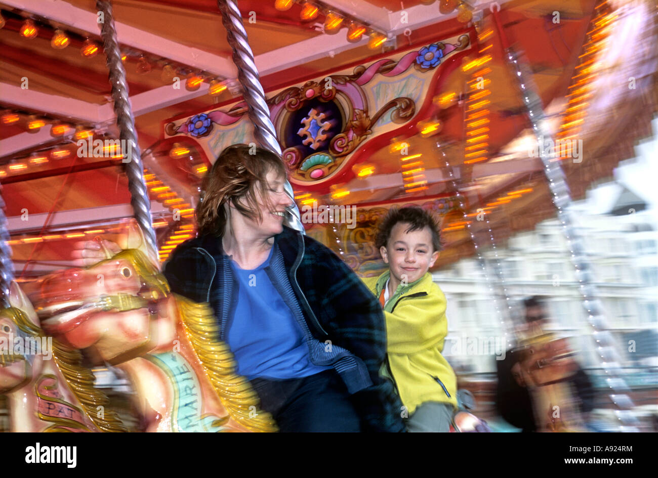Mother and son on a merry-go-round, Brighton seafront, East Sussex. - Stock Image