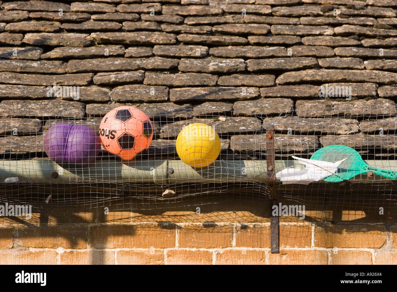 Playground toys such as balls and footballs lost in guttering on the school roof - Stock Image