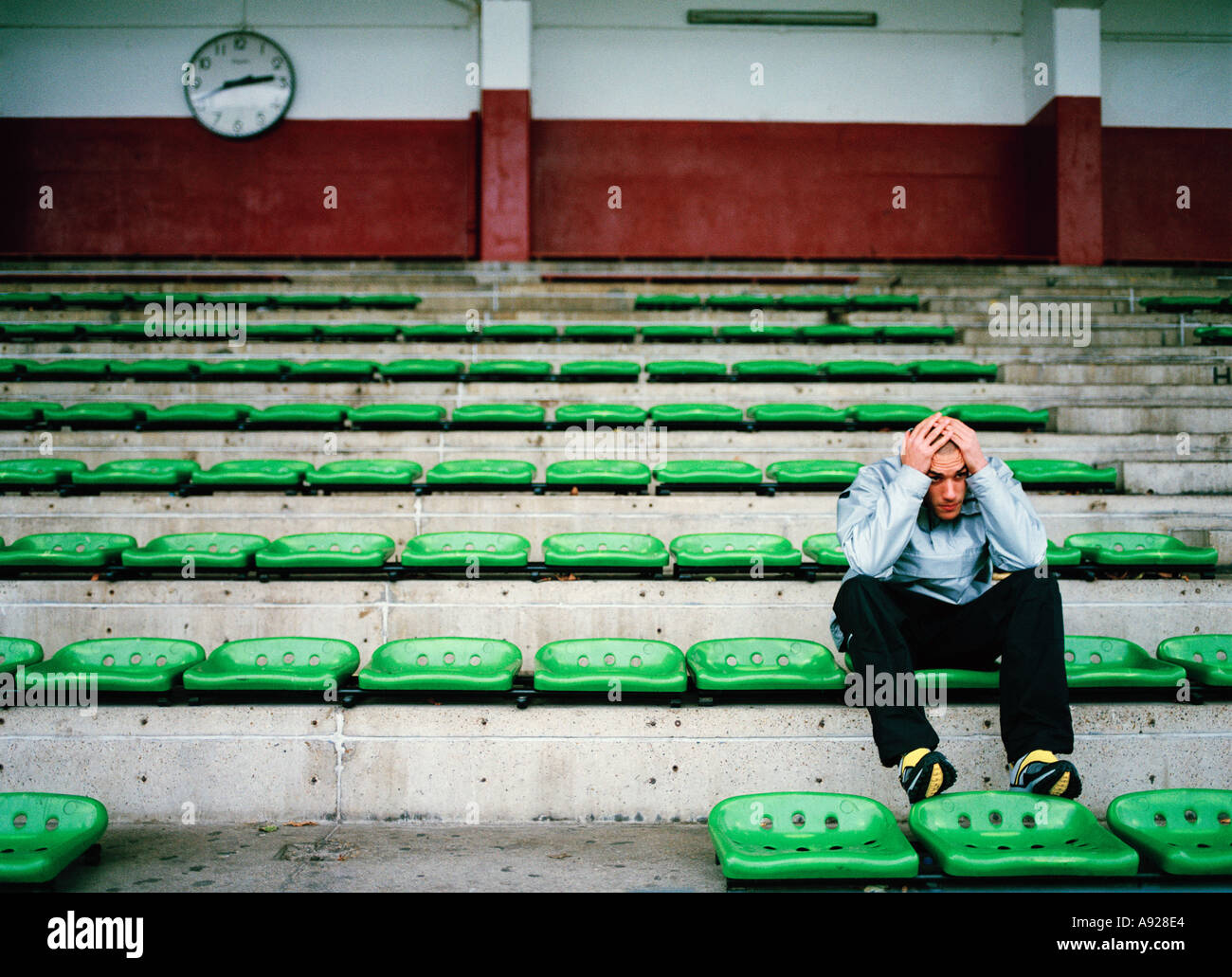 SAD LONELY YOUNG MAN IN STADIUM - Stock Image