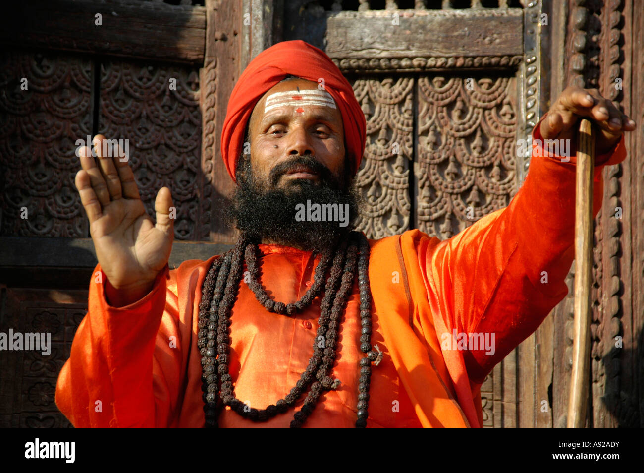 Holy man sadhu with many necklesses dressed in shining orange robe Kathmandu Nepal Stock Photo