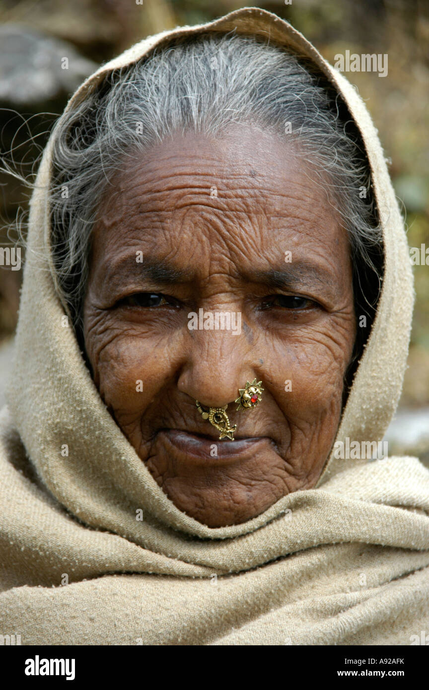 Portrait of an old lady with a pierced nose in the hood near Pokhara Nepal Stock Photo