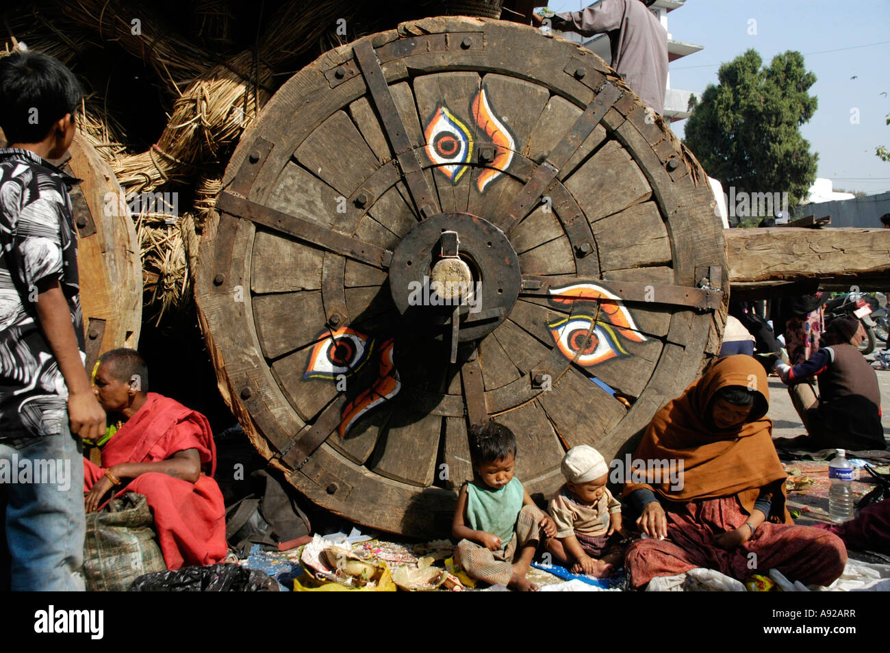 Mother with children sit at the wooden wheel of the chariot of Seto Macchendraonath Kathmandu Nepal - Stock Image