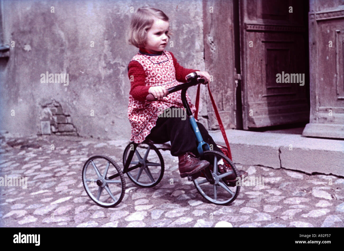 Historical picture child with a tricycle playing in the street 1960 - Stock Image