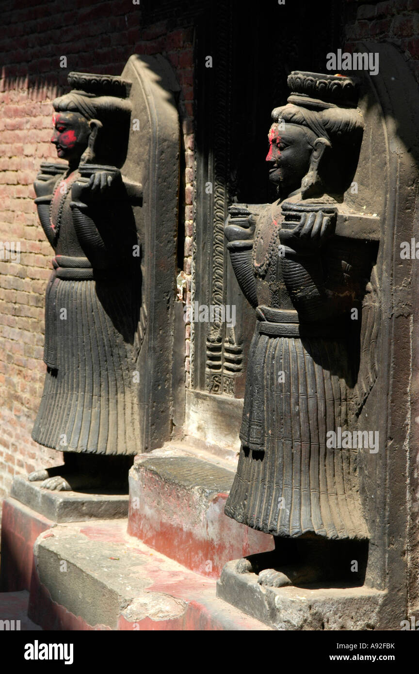 Two figures with red coloured cheeks Royal Palace Bhaktapur Nepal - Stock Image
