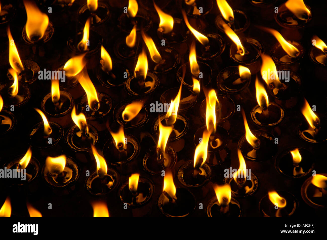 Burning flames of butter lamps in the darkness Kathmandu Nepal - Stock Image