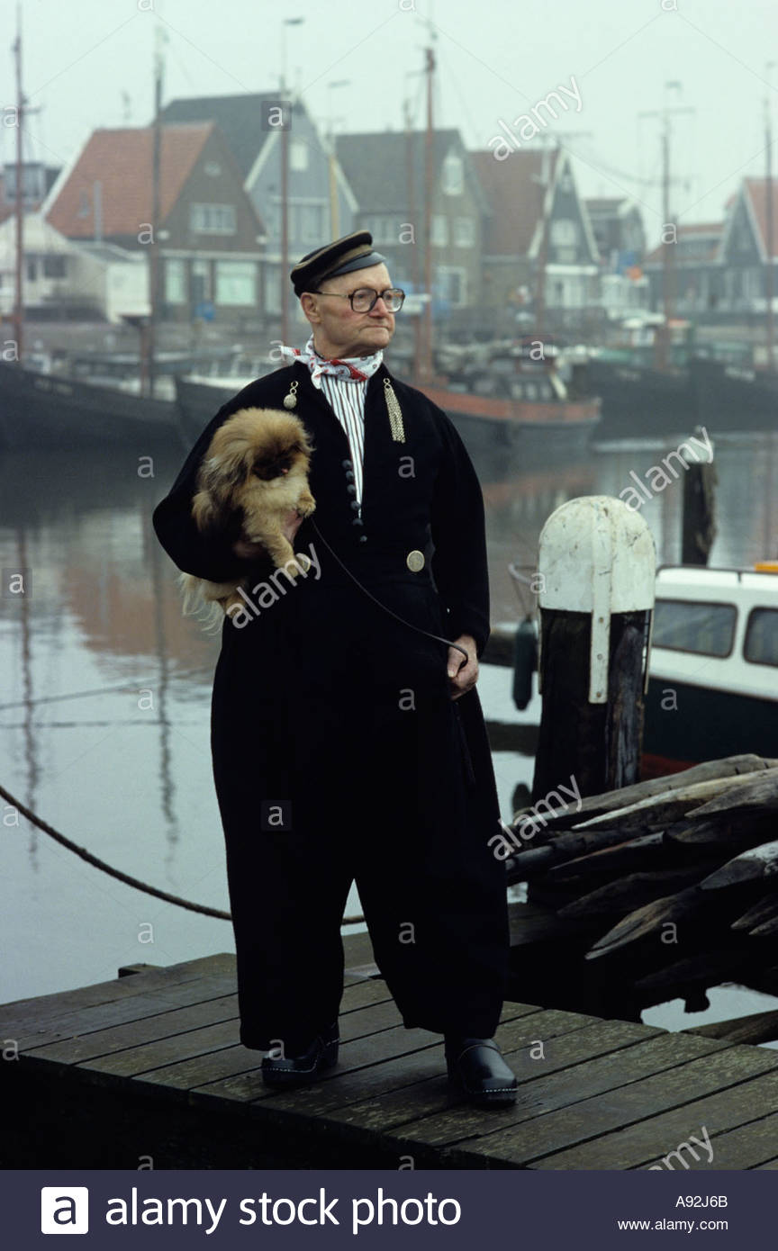Dutch man in traditional dress walking his dog in the