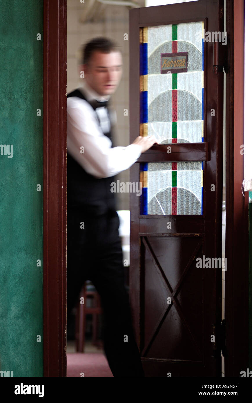 Waiter Coming Through the Kitchen Door of a Busy Restaurant ...