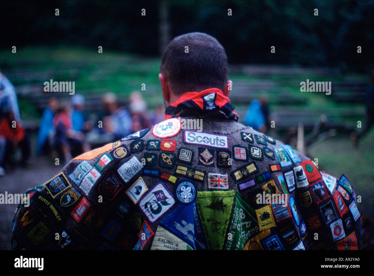 Scoutmaster wearing cape covered in badges from previous camps nr London England uk britain europe eu - Stock Image