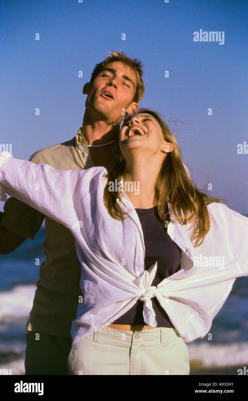 Young man and a teenage girl laughing on the beach - Stock Image