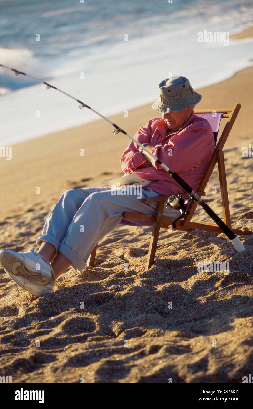 Senior Man Sitting On The Beach In A Deck Chair With A Fishing Rod