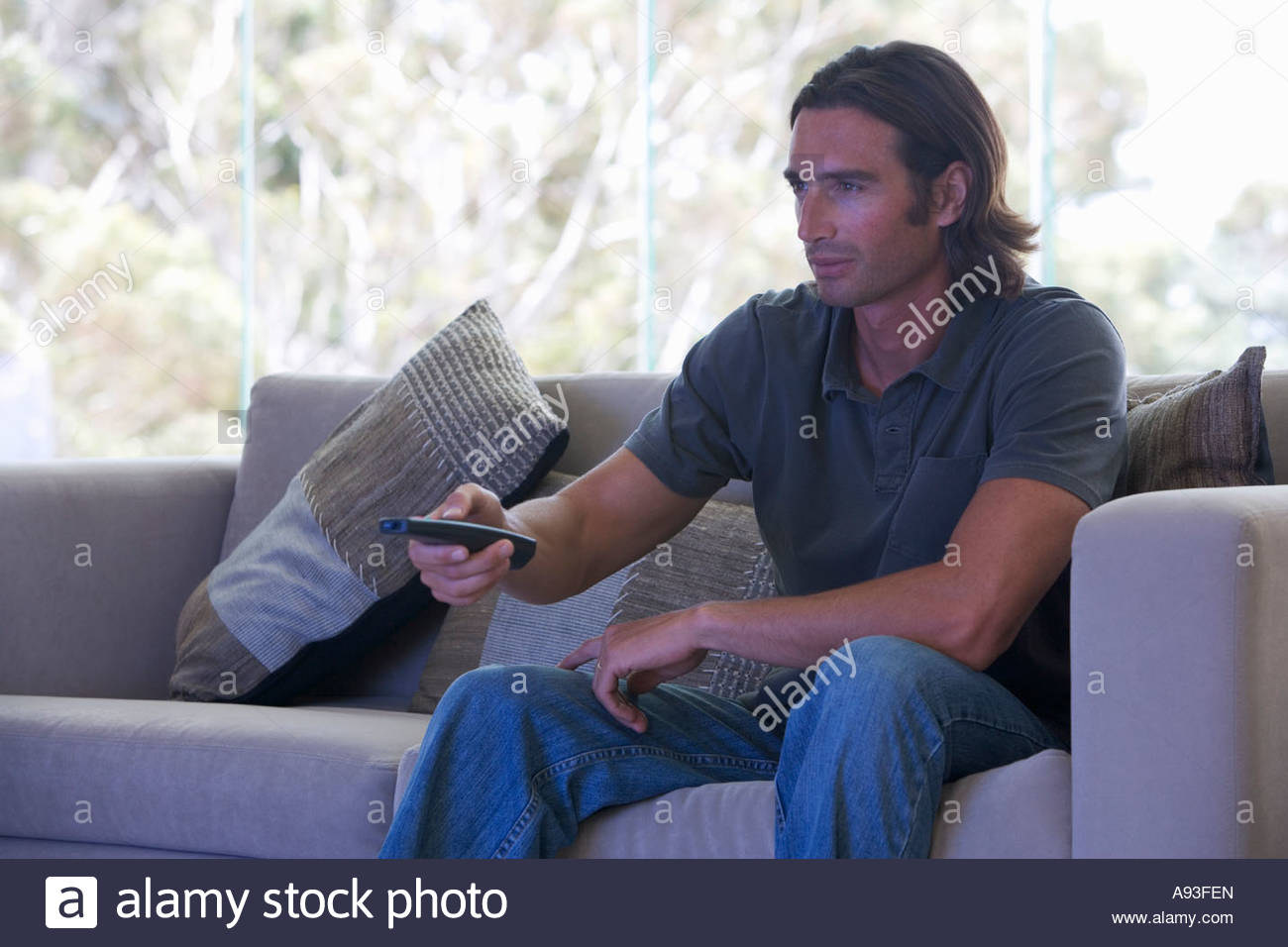 A man using a remote control watching tv - Stock Image