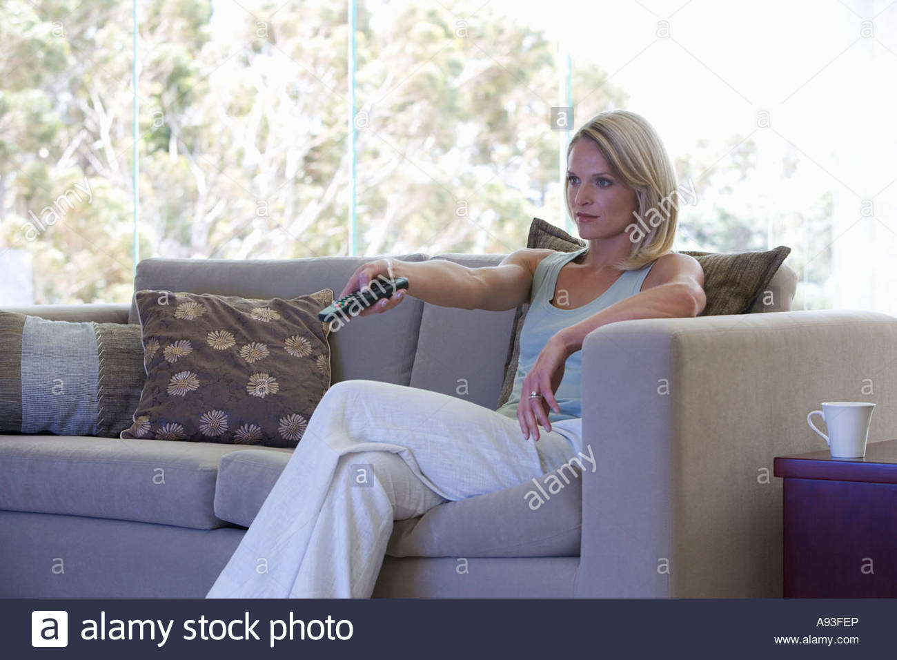 A woman using a remote control - Stock Image
