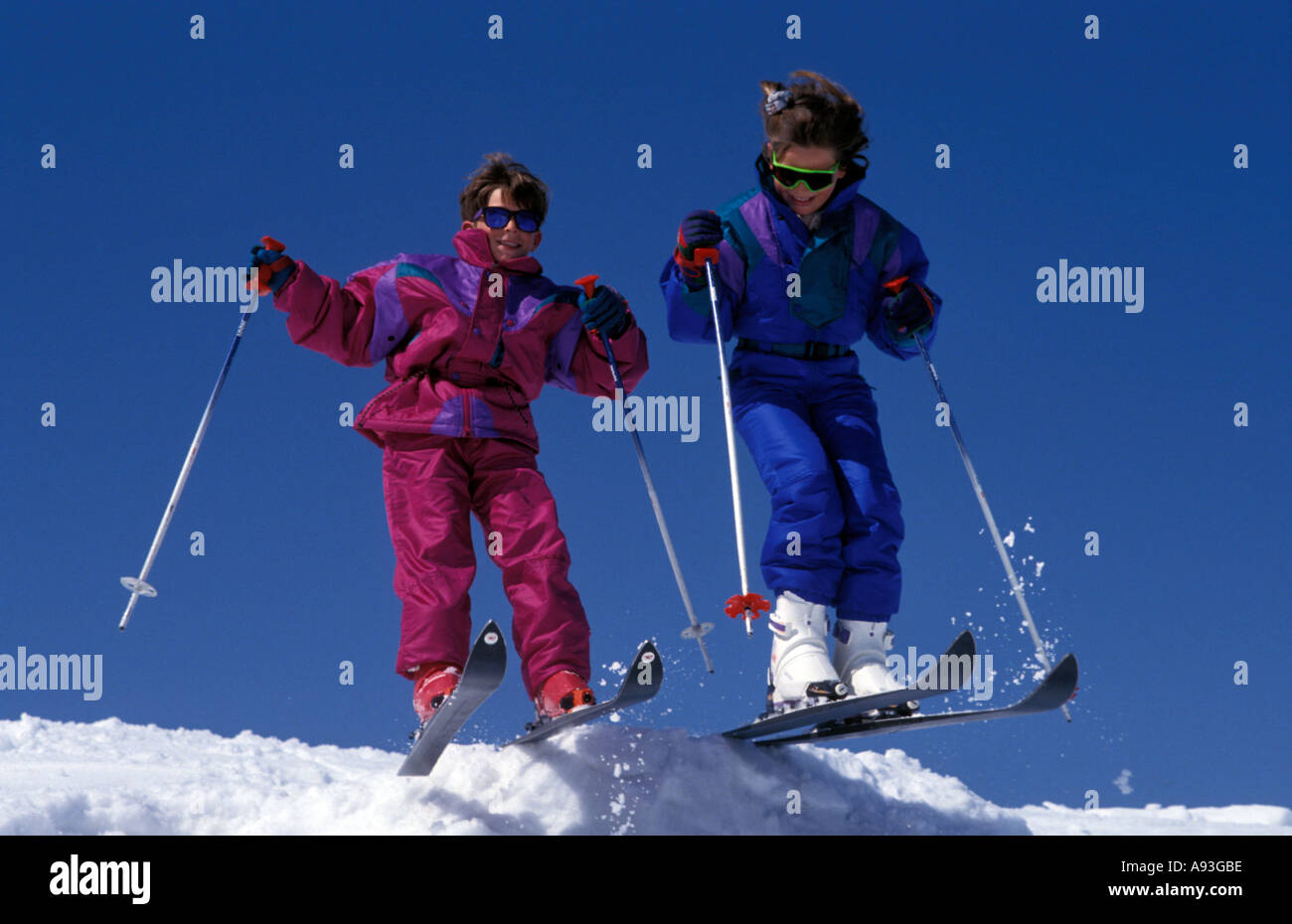 Two children aged about 8 in ski suits skiing over ridge of slope - Stock Image