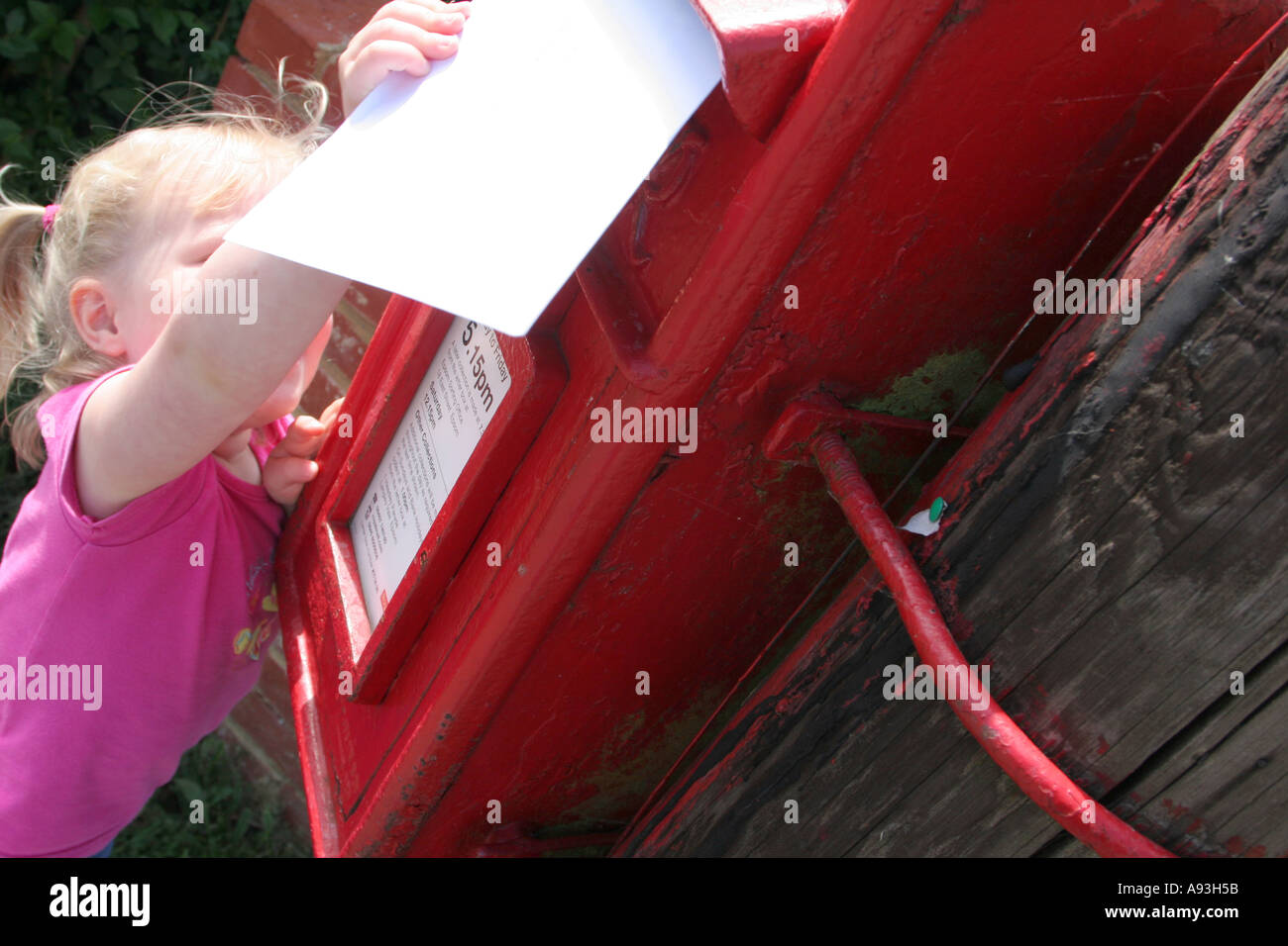 young girl posting letter in village - Stock Image