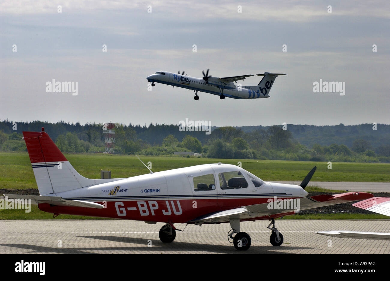 Flybe plane taking off from Southampton Airport and light aircraft waiting on runway. - Stock Image