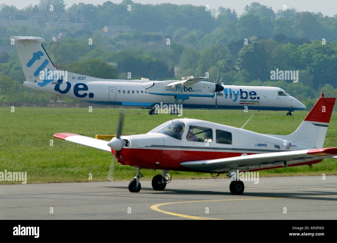 Flybe plane landing at Southampton Airport and Piper Cherokee light aircraft waiting on runway. - Stock Image