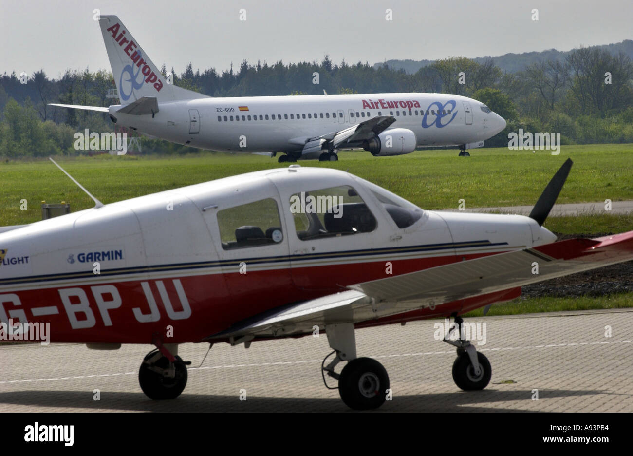 AirEuropa plane landing at Southampton Airport with light aircraft on runway in foreground - Stock Image