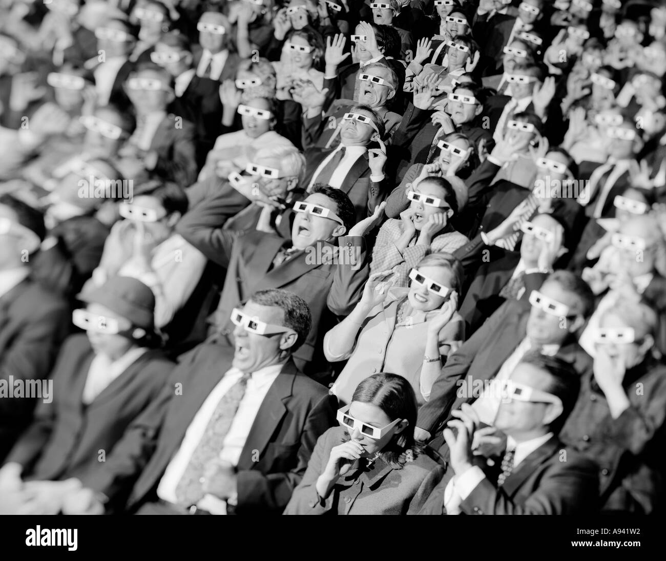 High angle view of a group of spectators sitting in a movie theater wearing 3-D glasses - Stock Image