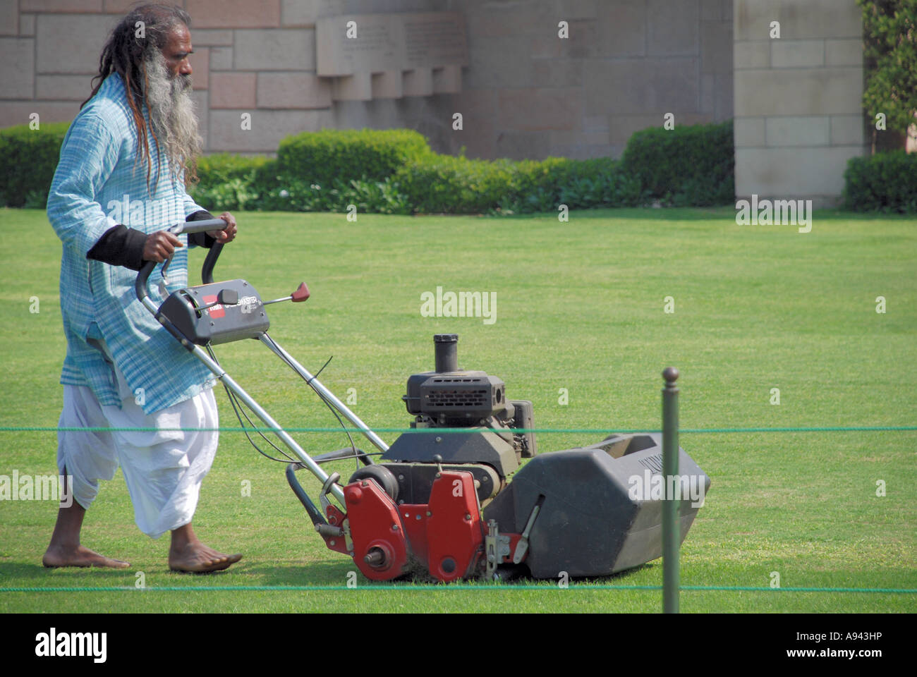 Old indian man cutting the grass - Stock Image