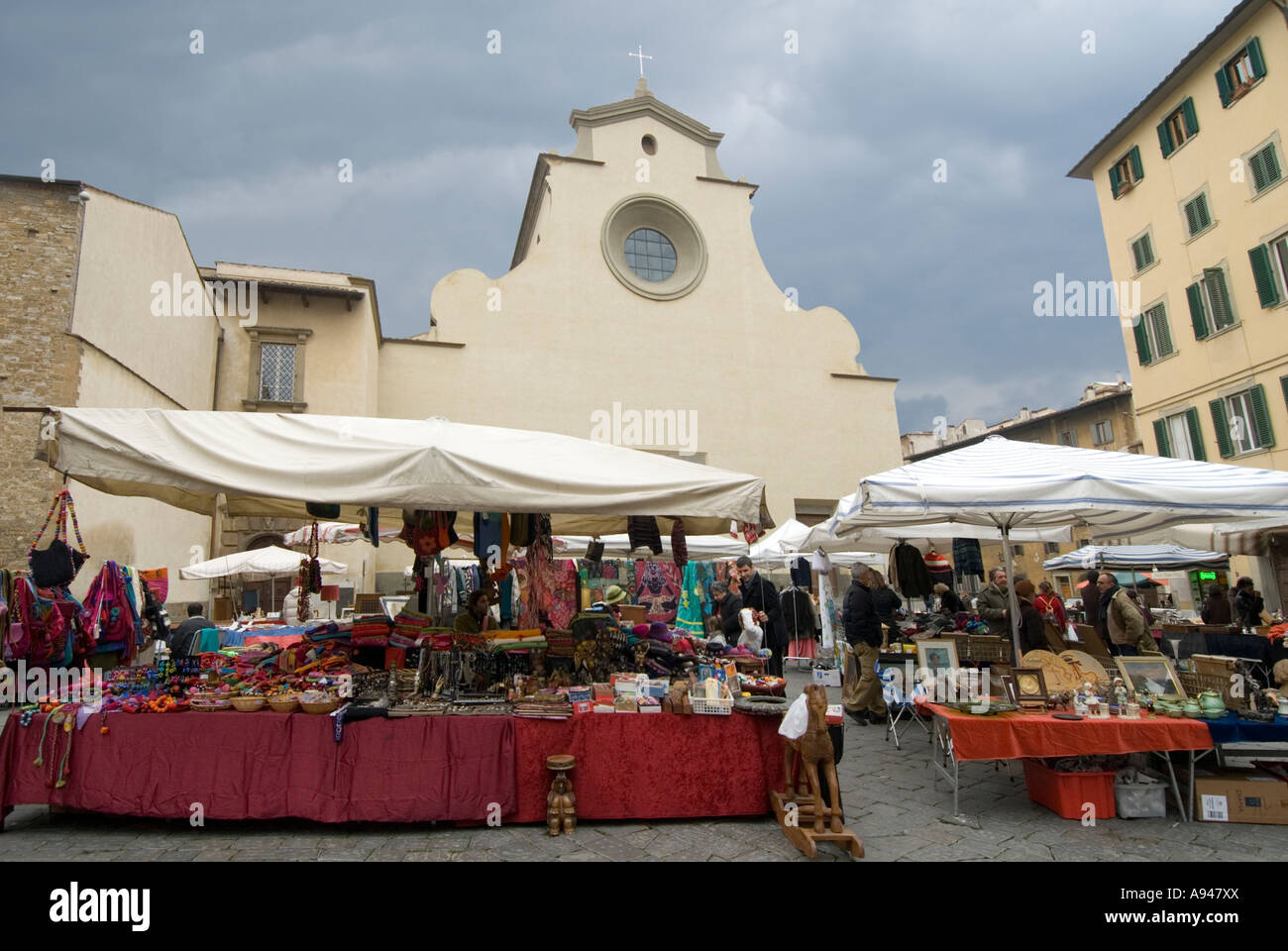 Horizontal wide angle of stalls at the Sunday market in Piazza di Santo Spirito on a stormy day. - Stock Image