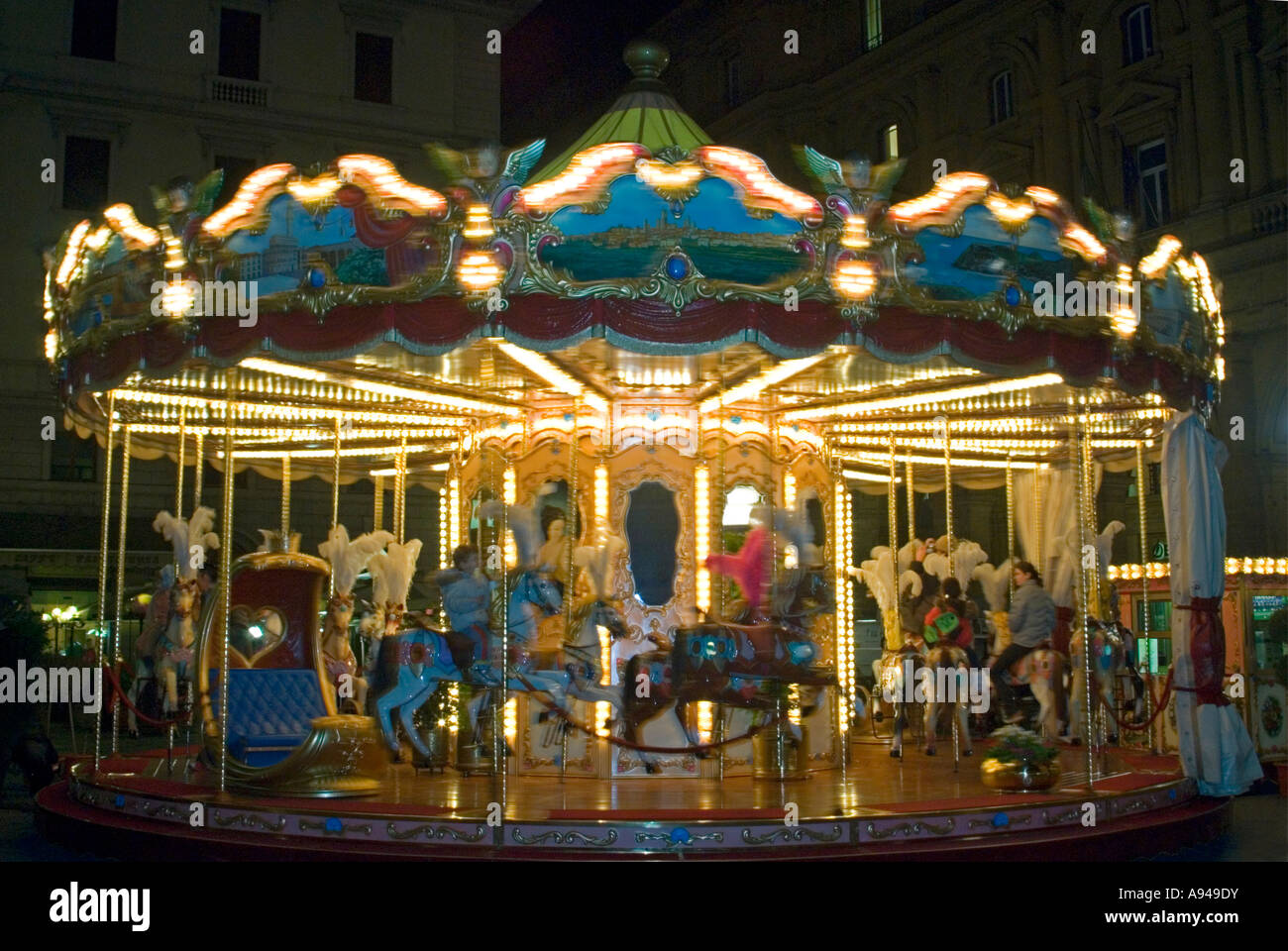 Horizontal close up of a bright glitzy old fashioned carousel at night, with motion blur as it rotates. Stock Photo