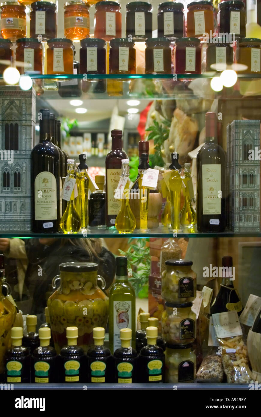 Vertical close up of many Tuscan delicacies in various bottles, jars and packets displayed in a shop window - Stock Image