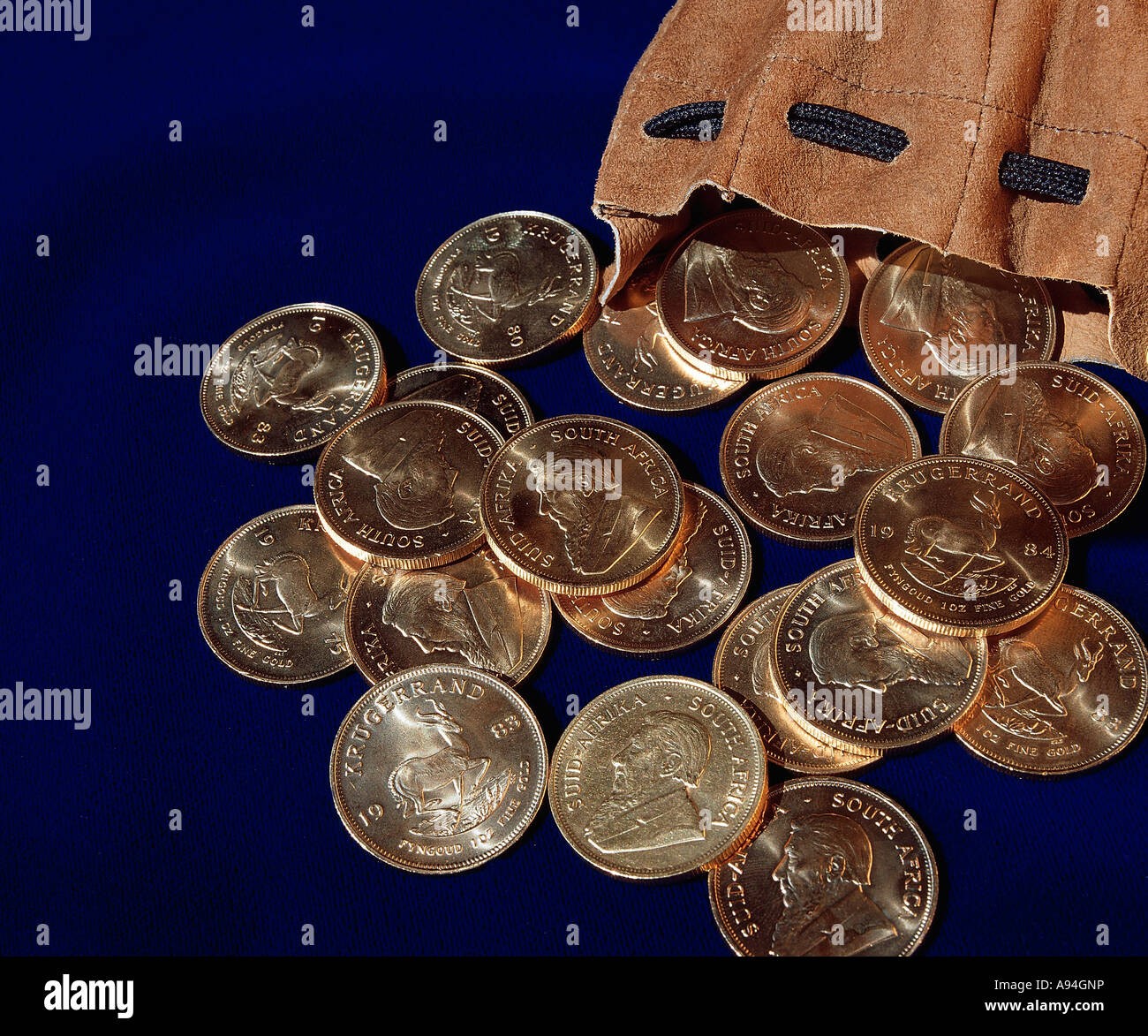 Kruger Rand Gold coins lie spilled from a leather pouch Johannesburg Gauteng South Africa - Stock Image
