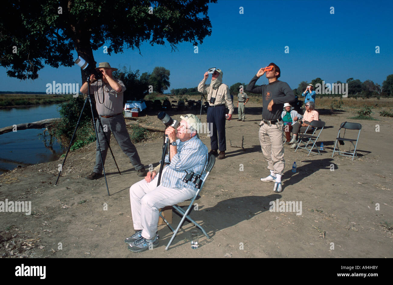 Tourists watch the 2001 full solar eclipse through cameras and telescopes shielded with devices - Stock Image
