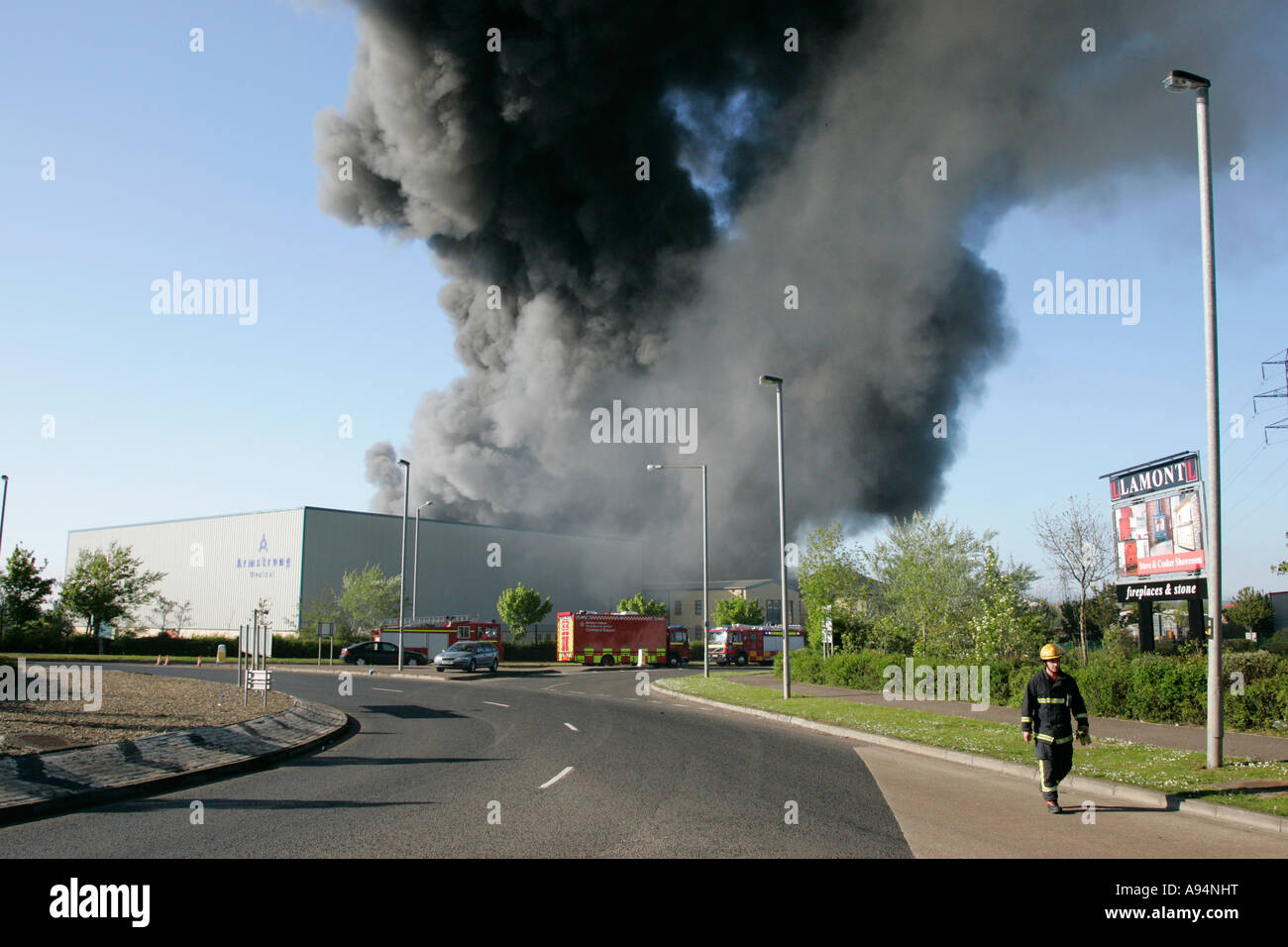 firefighter walks away from huge plume of smoke rising over fire at medical warehouse coleraine - Stock Image