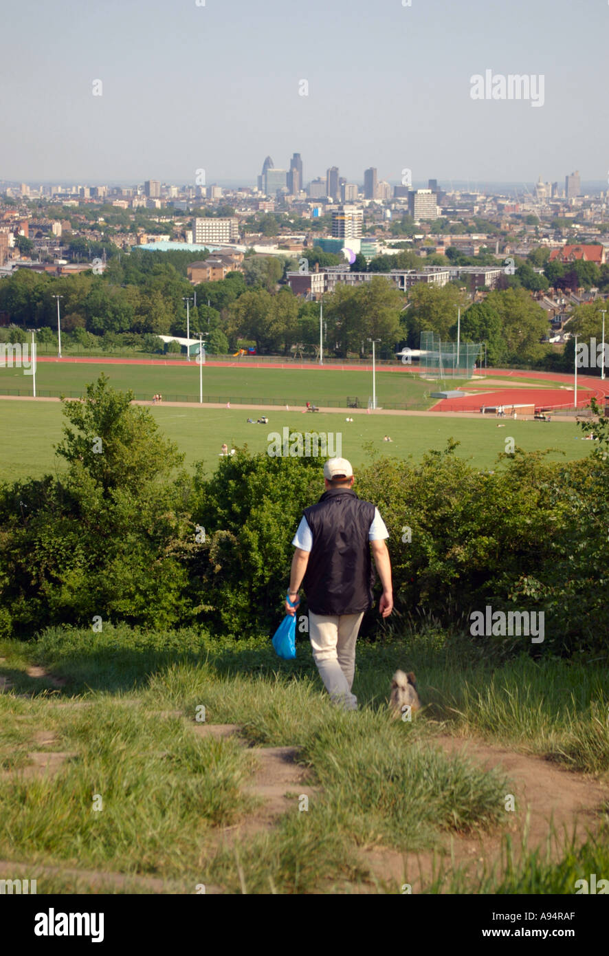 man walking dog on Parliament Hill Hampstead Heath with view over London Stock Photo