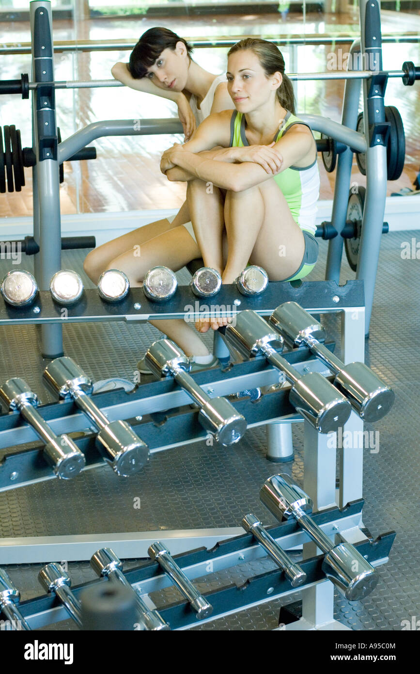 Two young women sitting in weight room - Stock Image