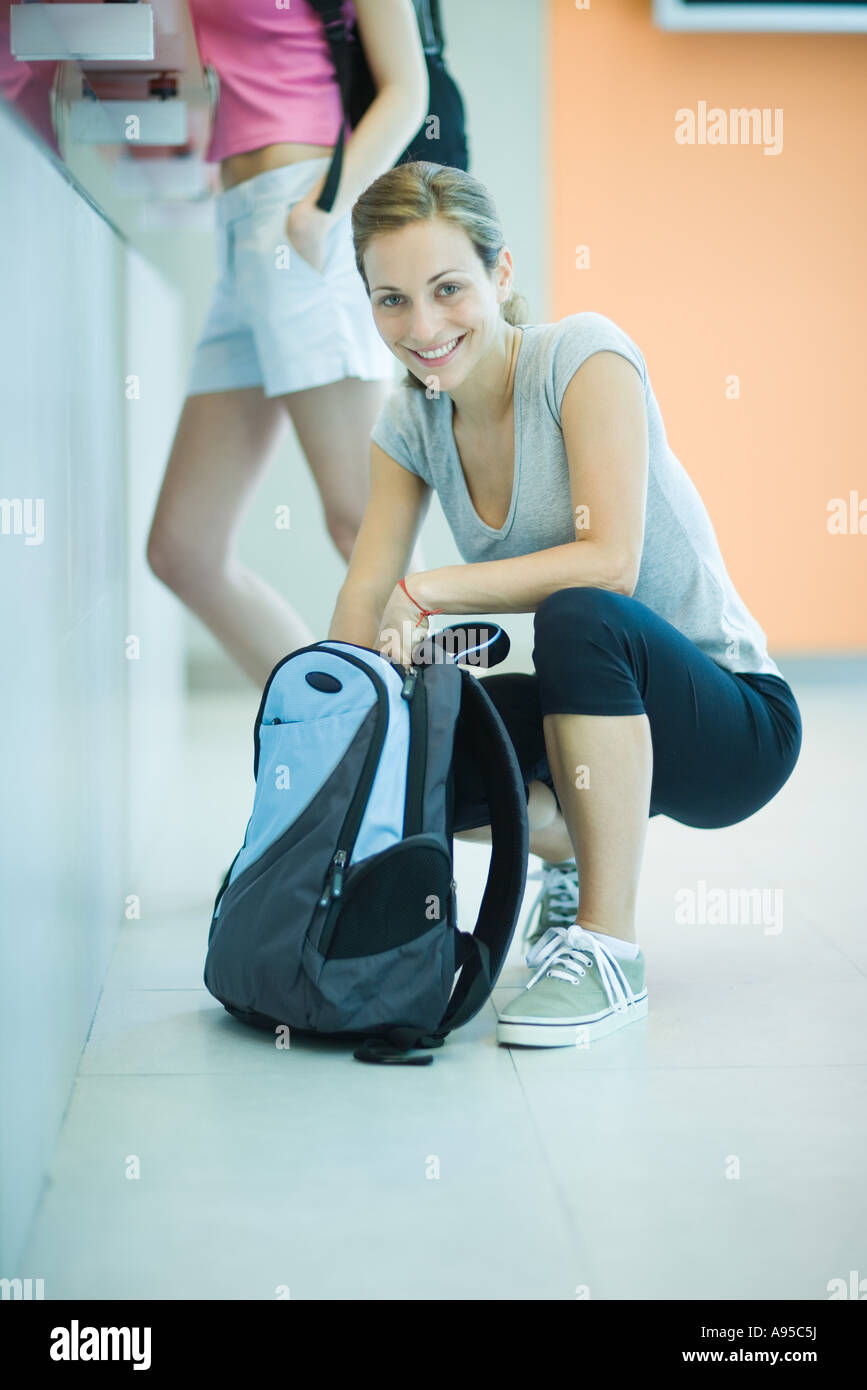 Young woman by counter at health club, squatting down, looking through backpack - Stock Image