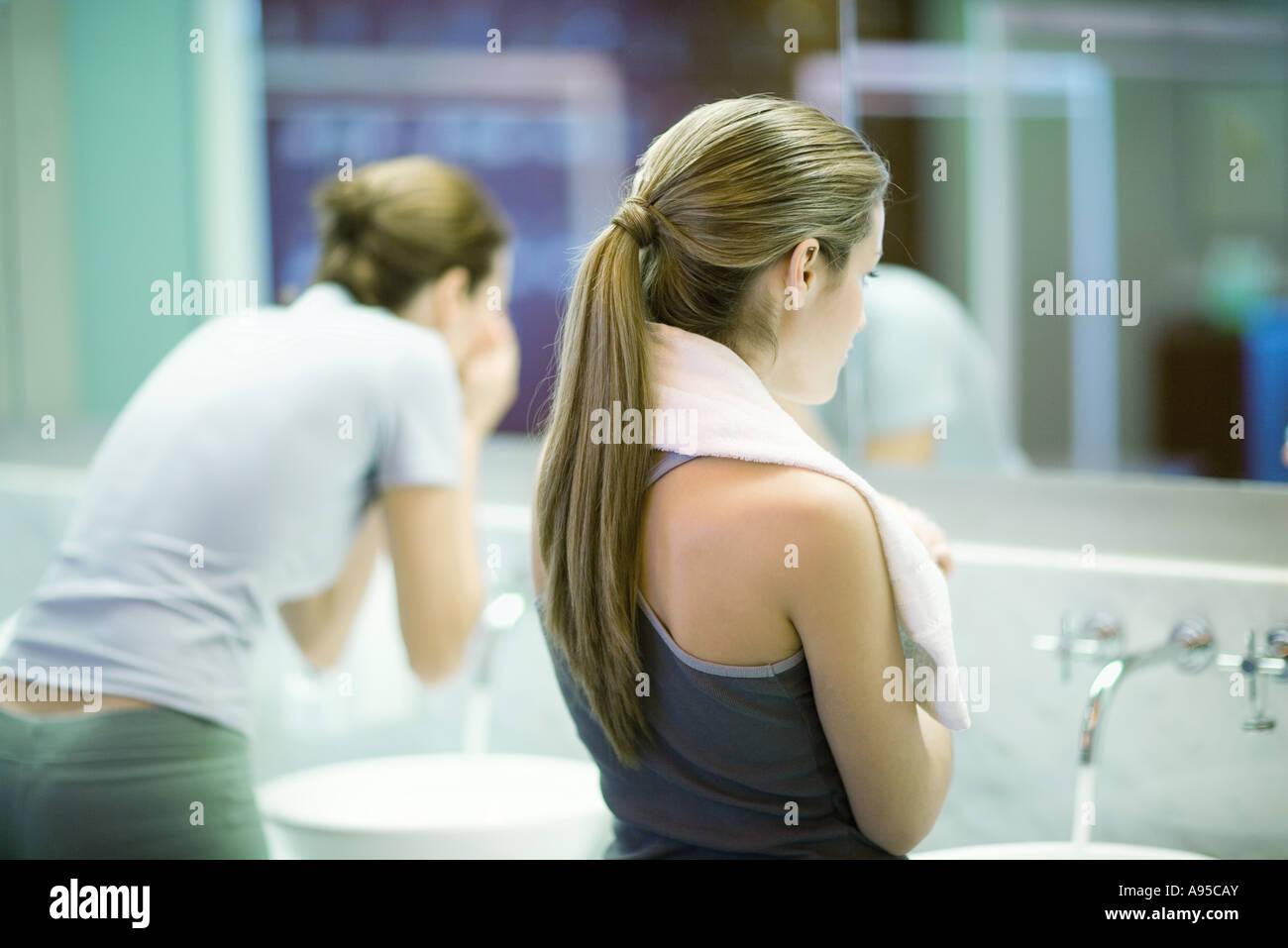 Women in public restroom, facing mirror - Stock Image