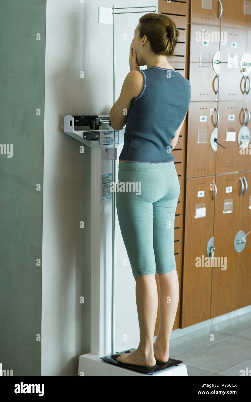 Young woman standing on scale in locker room, covering mouth - Stock Image