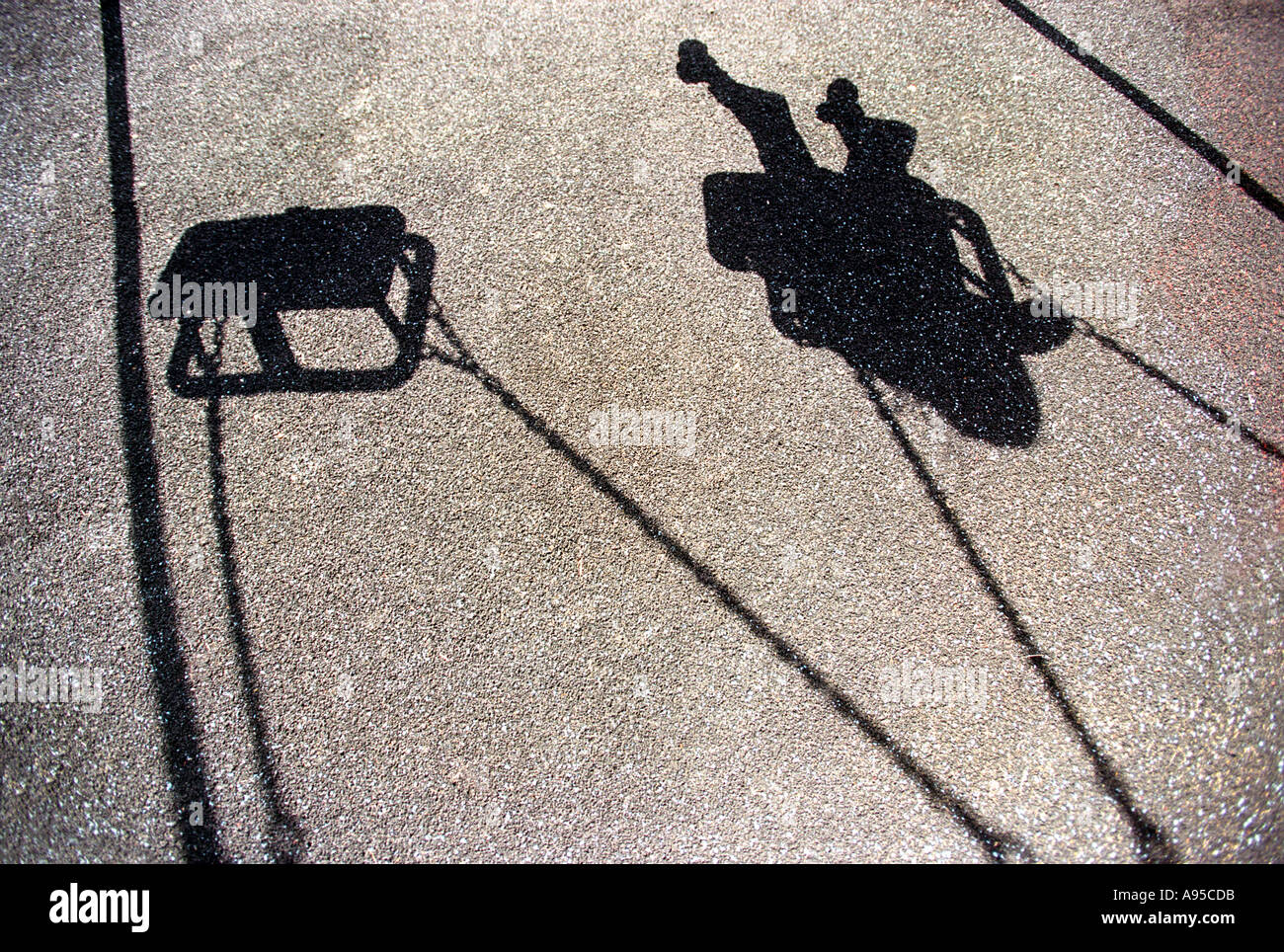 The shadow of a young girl or boy playing on a swing Stock Photo