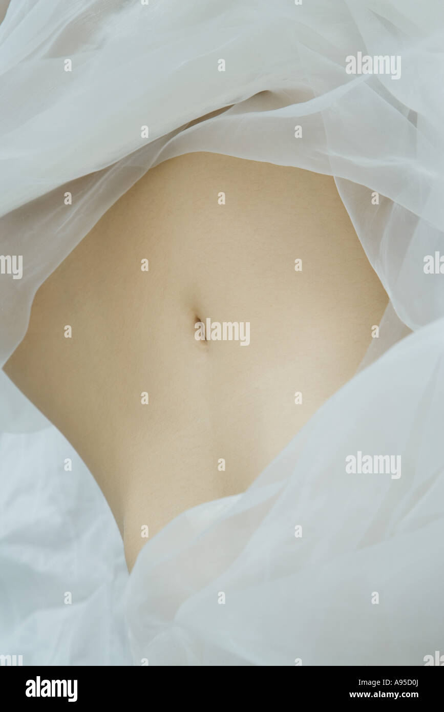 Woman's abdomen, surrounded by sheer fabric, full frame - Stock Image