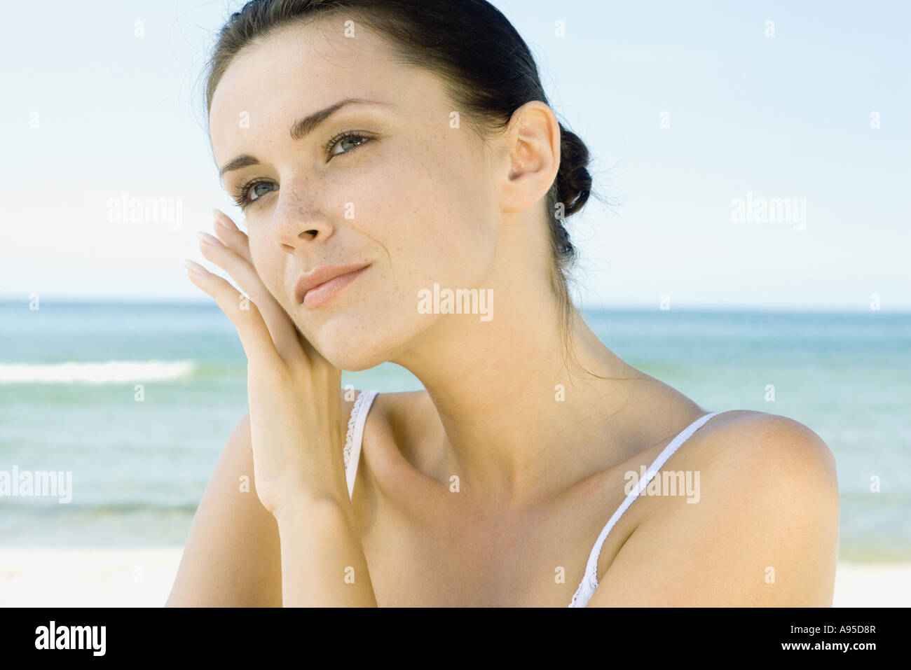 Woman touching face with back of hand, sea in background, head and shoulders - Stock Image