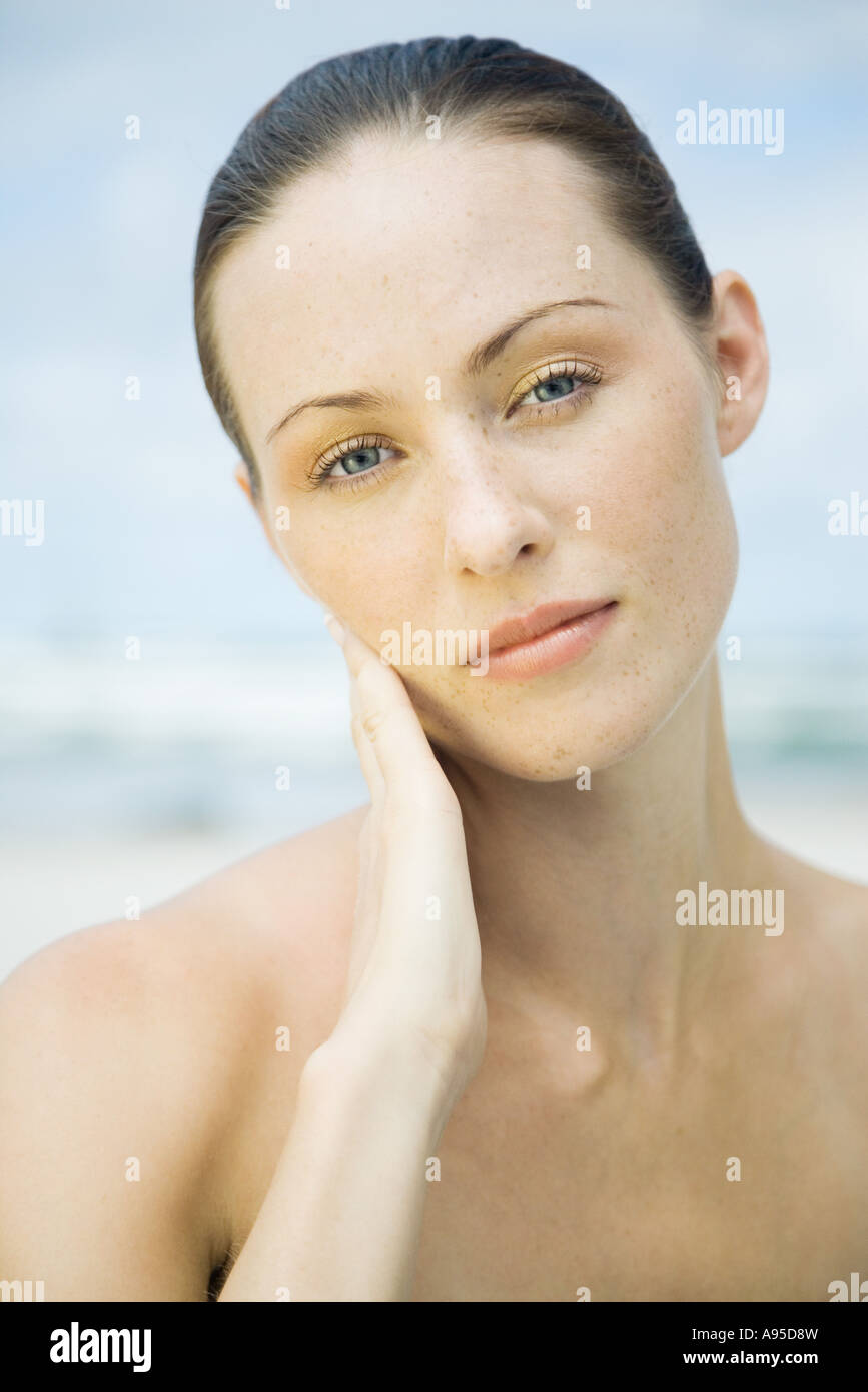 Woman touching cheek, head and shoulders, portrait - Stock Image