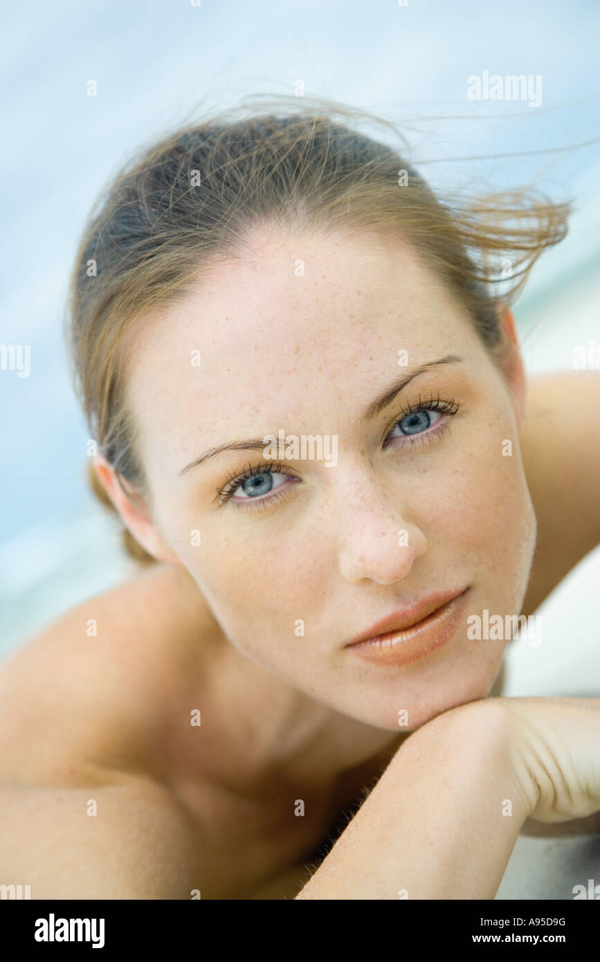Woman lying on beach, looking at camera, head and shoulders, close-up - Stock Image