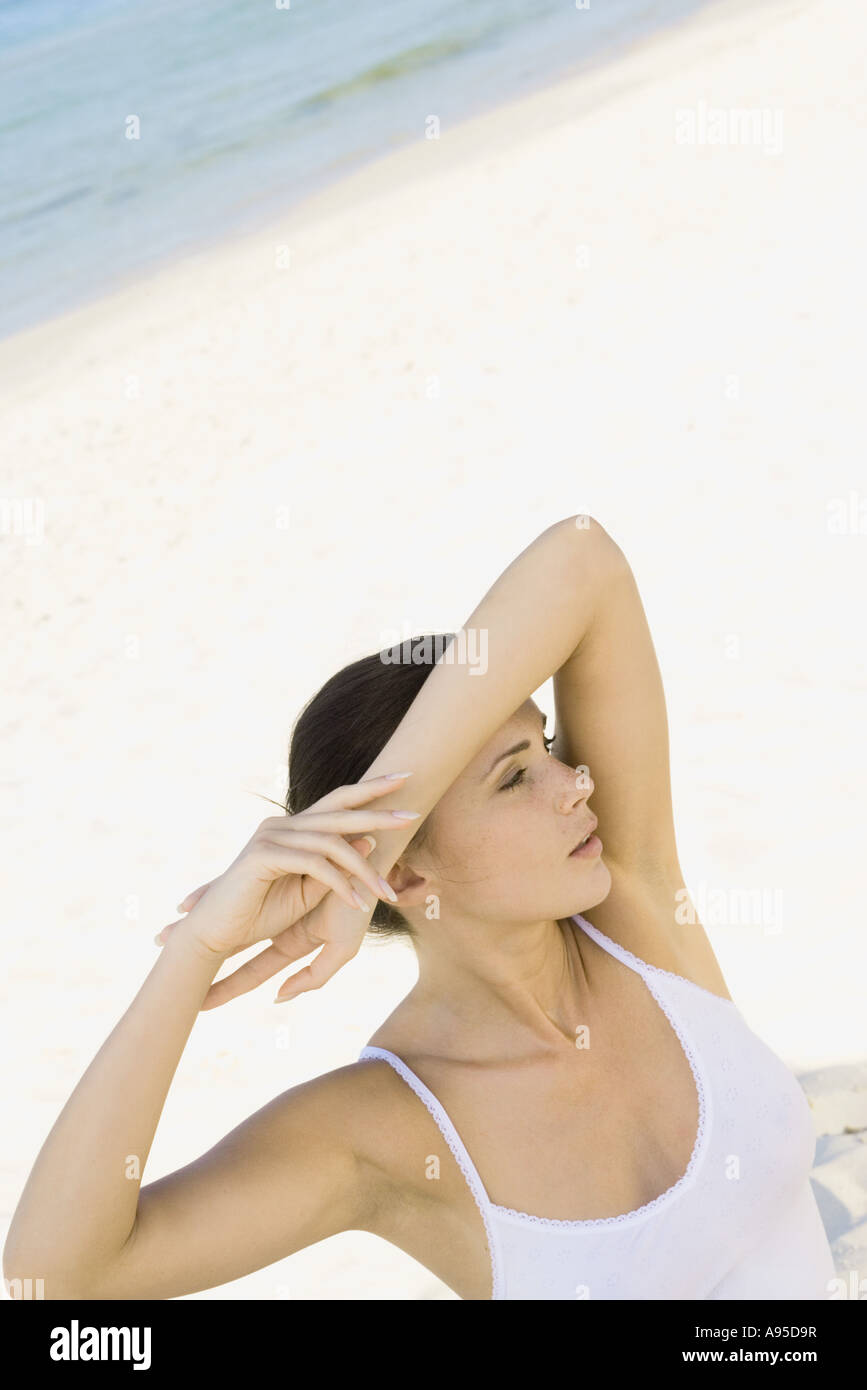Woman on beach, shading eyes with arm - Stock Image
